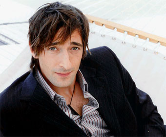 A typical Adrian Brody look: carefully tousled, clean shaven, expensive jacket, pendant on cord (sometimes a cravat)