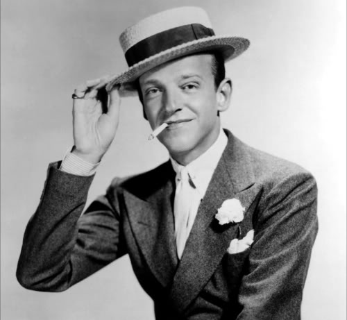 Fred Astaire, the original dandy, fully accessorized with cufflinks, collar pin and studs - not to mention carnation, pocket kerchief and boater.