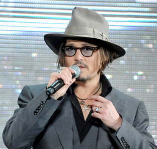 Johnny Depp at a premiere playing the bohemian dandy: conservative suit with rings, necklaces, fedora, toussled locks, tinted specs