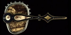 Hindsight pin, 1997 by Kiff Slemmons of found photographs, silver, clock hand, mica (collection of Helen Kornblum)